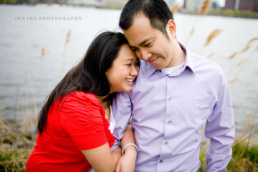 Charles River engagement session in Boston, MA - couple snuggling against reeds